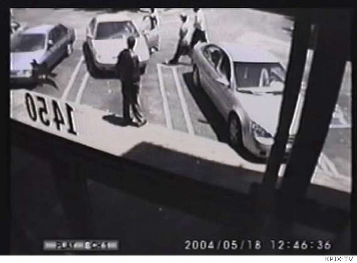 Freeze frames of a surveillance video shows the scene Tuesday of the killing of Chris Johnson in the parking lot of a strip mall in the Western Addition. Johnson's car is the middle vehicle, partially pulled out of a parking stall. Surveillance image via KPIX-TV