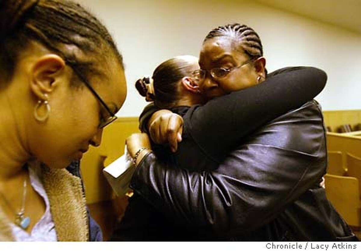 Malaika Parker, left waits as Mesha Irizarry hugs Susie McAllister, mother of a victim from an incident with the police on Martin Luther King Jr. Day , 2002 on Potrero Hill, as the police commission votes not to dismiss the charges against the police officer involved,during the meeting Wed. March 24, 2004, in San Francisco. LACY ATKINS / The Chronicle