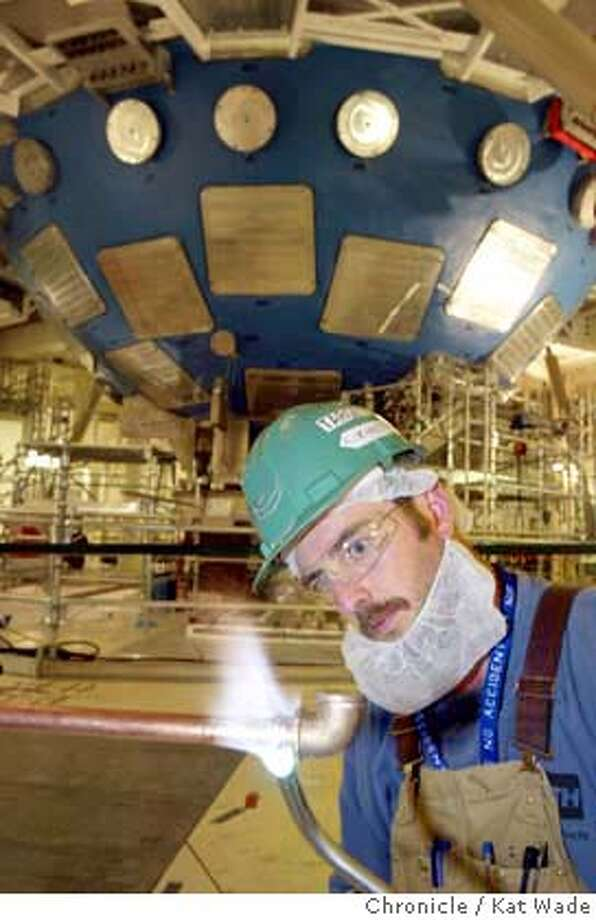 LABSa-C-17OCT02-MT-KW - Neal Fouts with Kenetics mechanical contractor welds some pipe with the huge target chamber of the new NIF (National Ignition Facility) at the Lawrence Livermore Lab in the background. SAN FRANCISCO CHRONICLE PHOTO BY KAT WADE CAT Photo: KAT WADE