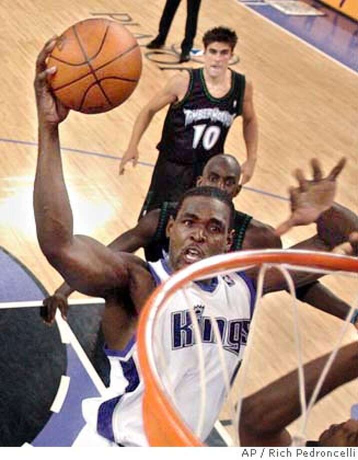 Sacramento Kings forward Chris Webber, left, goes up for the stuff over Minnesota Timberwolves Kevin Garnett, behind, as Wally Szczerbiak, background, watches during the fourth quarter of Game 6 of their Western Conference semifinal series in Sacramento, Calif. Sunday, May 16, 2004. The Kings beat the Timberwolves 104-87, to tie the series at 3 games apiece with Game 7 to be played in Minnesota.(AP Photo/Rich Pedroncelli) Photo: RICH PEDRONCELLI