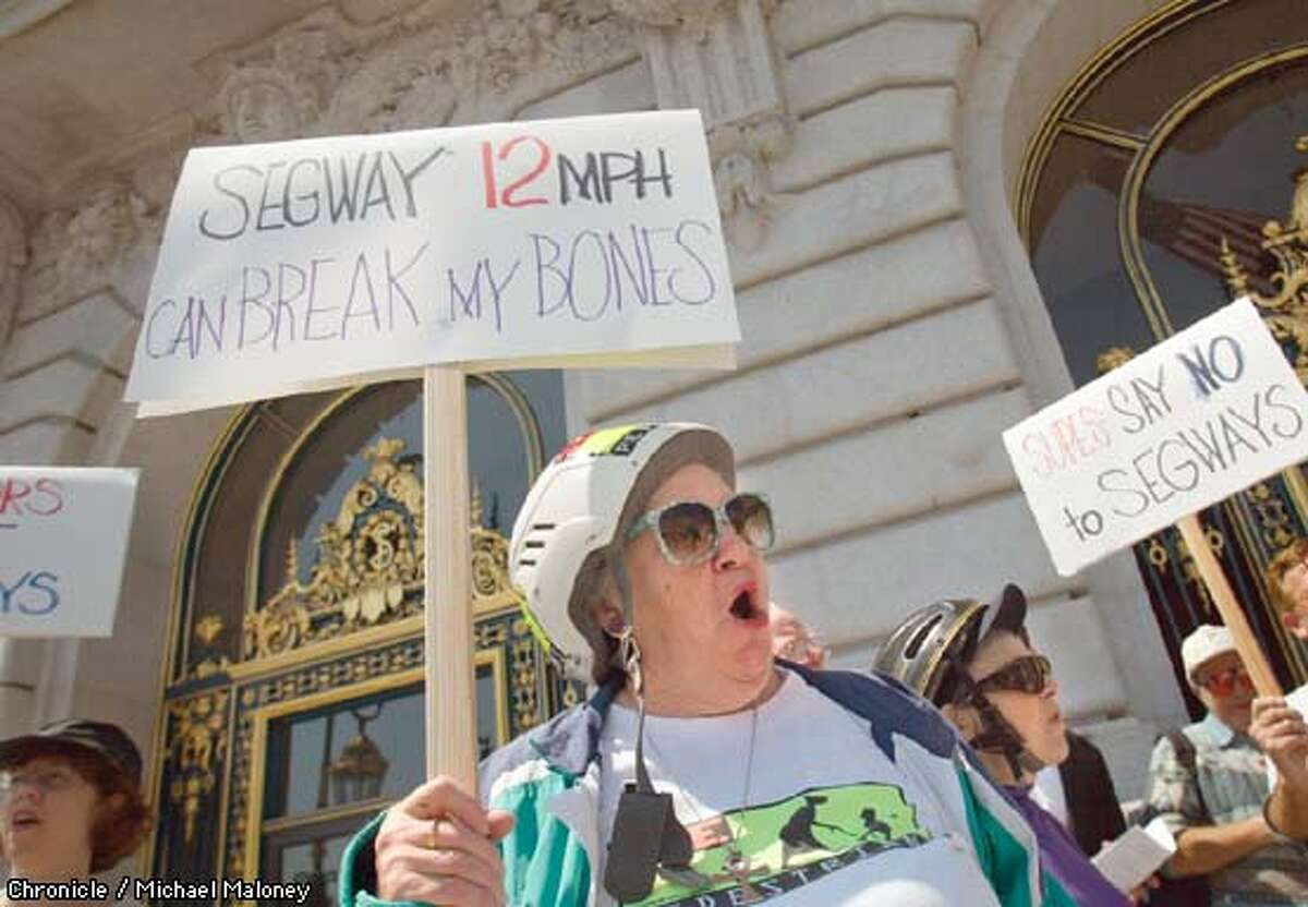 Wearing helmets for the demo, Senior Action Network members Jeanne Lynch (73) center and Shirley Bierly (78) both of SF spoke at the rally. Both have been injured by bicyclists riding on sidewalks and both feel the segway should also be banned from the sidewalks. Senior citizens from the activist group Senior Action Network protested a proposal to allow segways on the sidewalks of SF. A small group of less than 2 dozen held a press conference on the steps of SF City Hall at noopn. CHRONICLE PHOTO BY MICHAEL MALONEY