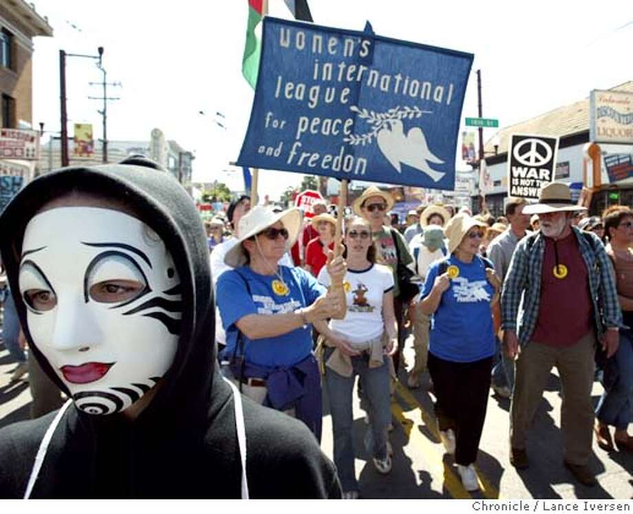 PROTEST21125_LI.JPG  event on 3/20/04 in SAN FRANCISCO Wearing a mask Laura Venturi from Berkeley joined thousands as they march along Mission Street Saturday. Anger over the war in Iraq remained sharp on the first anniversary. By Lance Iversen The San Francisco Chronicle Photo: Lance Iversen