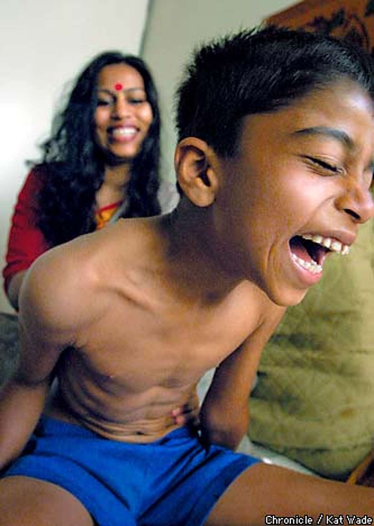 Awakening: Pratichi Mathur gives her son, Dhruv, 7, his morning massage with sesame oil, turmeric root and brahmi leaves prepared for his dominant dosha, pitta. Chronicle photo by Kat Wade