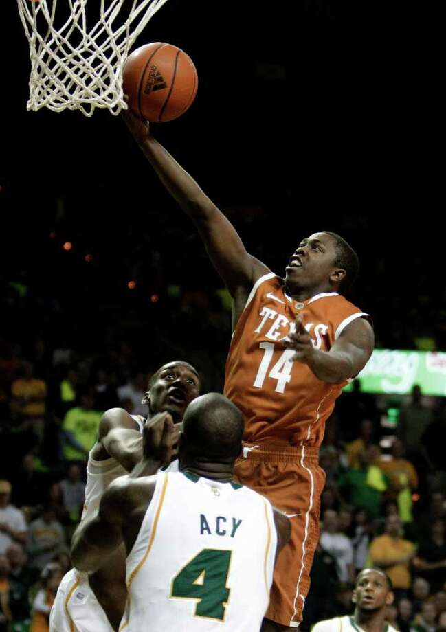 Texas 's J'Covan Brown (14) goes up for a shot over Baylor 's Quincy Acy (4)  and Quincy Miller, rear, during the first half of an NCAA college basketball game. Saturday, Jan. 28, 2012, in Waco, Texas. (AP Photo/Tony Gutierrez) Photo: Tony Gutierrez, Associated Press / AP