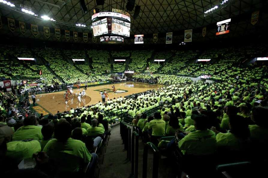 Baylor fans wear bright green shirts as their team takes on Texas in the first half of an NCAA colle
