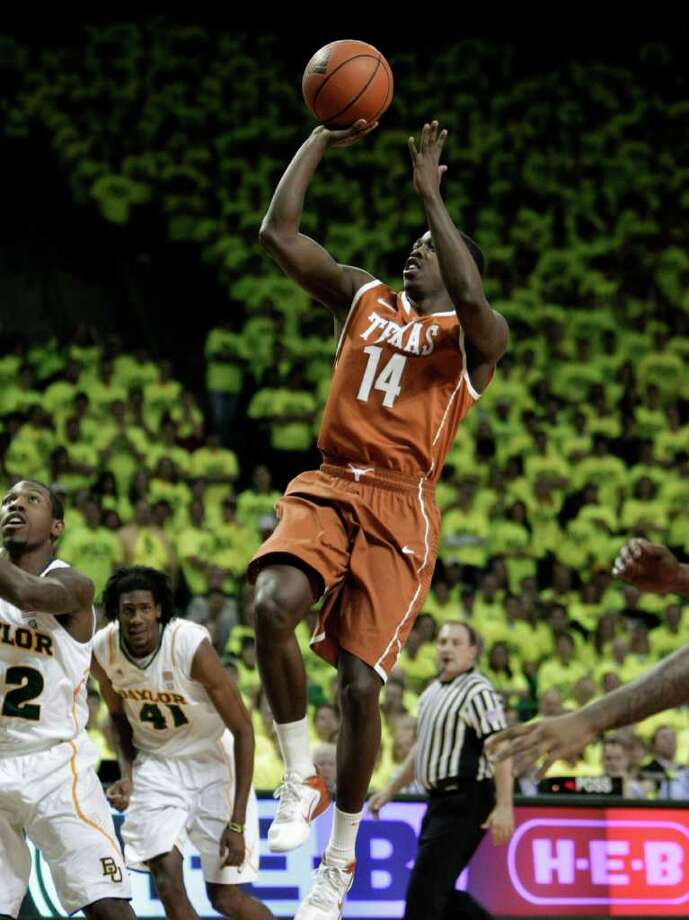 Texas 's J'Covan Brown (14) attempts a shot as A.J. Walton, left, and Baylor 's Anthony Jones (41) look on in the first half of an NCAA basketball game Saturday, Jan. 28, 2012, in Waco, Texas. (AP Photo/Tony Gutierrez) Photo: Tony Gutierrez, Associated Press / AP