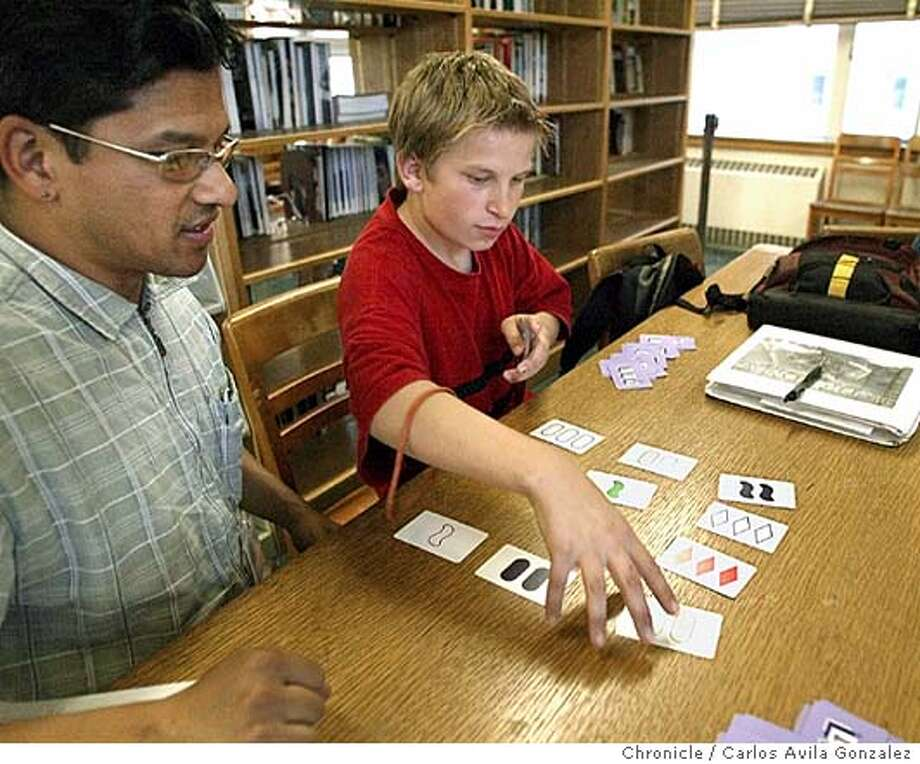 "Ajit De Silva, left, and Sanel Halilobic, play ""Sets"" a card game in the Oakland Library on Wednesday, April 28, 2004. Sanel and his brothers are refugees from Bosnia. Refugee Transitions started an East Bay tutoring program last fall for refugee kids from Cambodia, Bosnia and Afghanistan. So far, they�ve got 11 volunteers helping 13 youth in Oakland and Fremont with homework and adjustment issues. They hope to serve 60 kids by the end of the summer.  Photo taken on 04/28/04, in Oakland, CA.  Photo By Carlos Avila Gonzalez / The San Francisco Chronicle Photo: Carlos Avila Gonzalez"