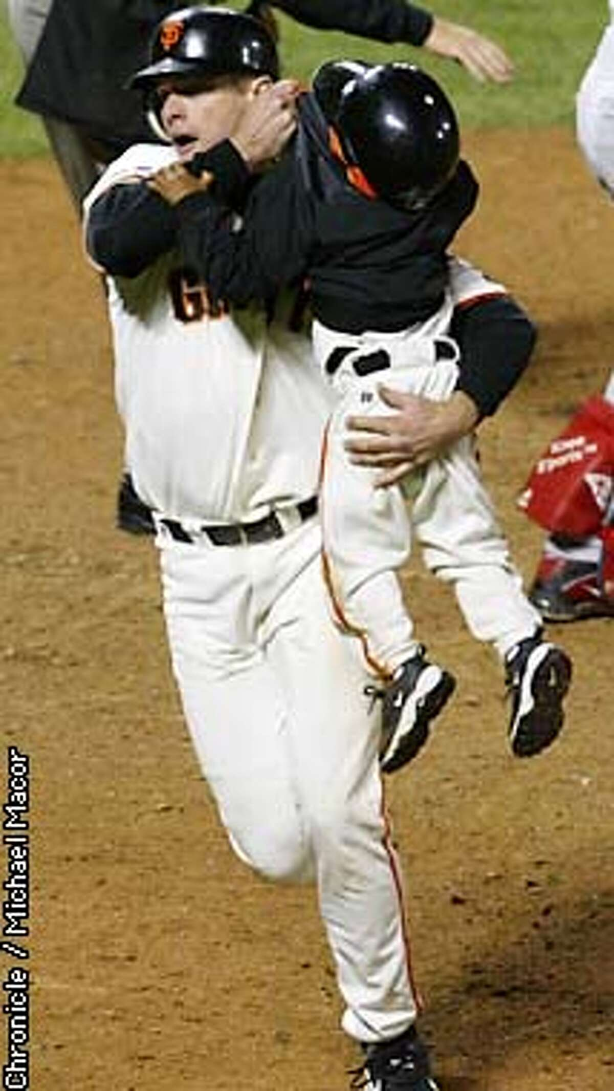 GIANTS67-C-24OCT02-SP-MAC --- J.T. Snow grabs a hold of Dusty Baker's 3-year old son Darren, as he came dangerously close to home plate as David Bell was about to cross the plate after Snow. The San Francisco Giants play the Anaheim Angels in Games 5 of the World Series at Pac Bell Park in San Francisco, Ca. October 24, 2002. Michael Macor/San Francisco Chronicle