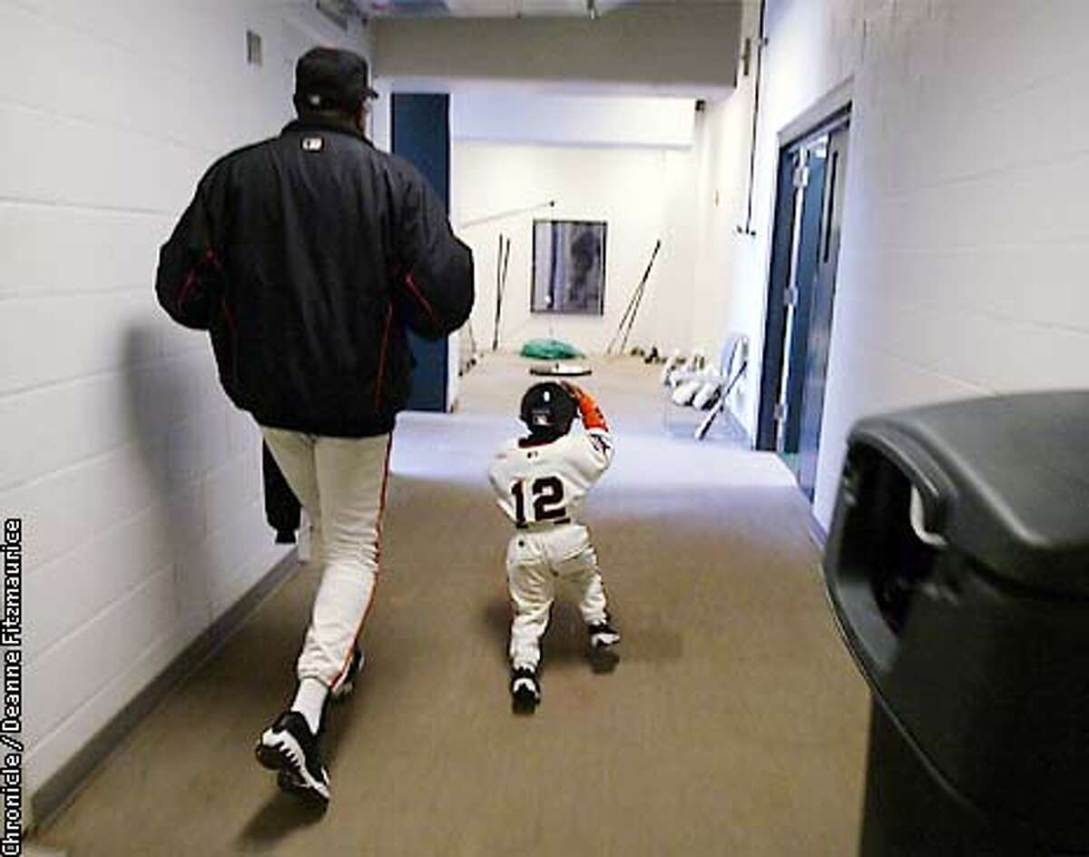 GIANTS3-C-25OCT02-SP-DF Darren Baker, 3, and his father San Francisco Giants' manager Dusty Baker, walk out of the clubhouse to the field at the start of game 4 of the World Series at Pacific Bell Park in San Francisco. Later, during game 4 Darren was rescued by JT Snow from the oncoming baserunner while retrieving a bat while batboy. CHRONICLE PHOTO BY DEANNE FITZMAURICE