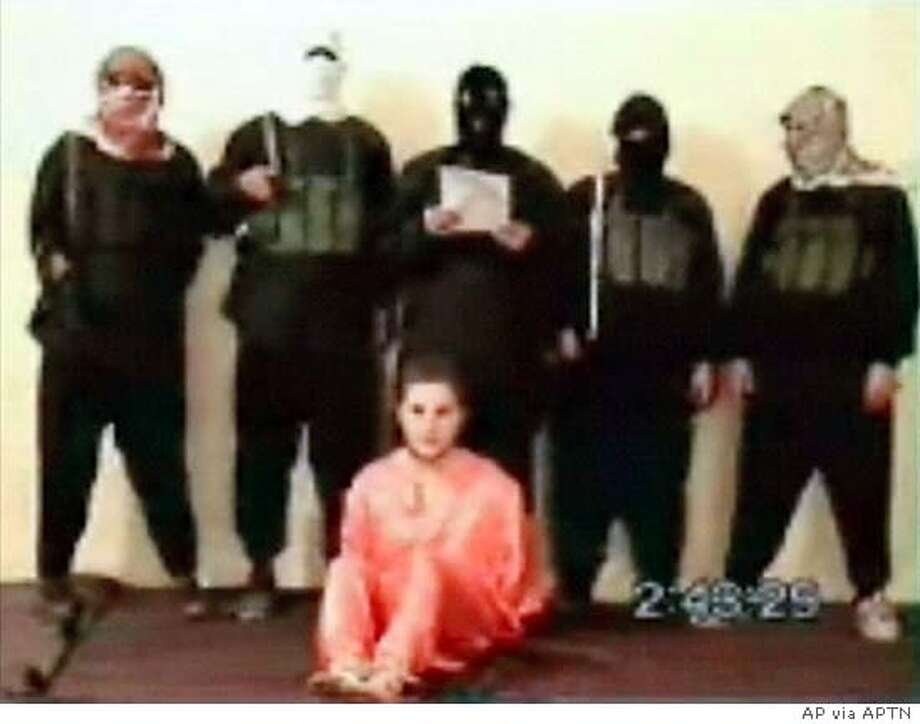 This is a image made from a video posted Tuesday May 11, 2004 on an Islamic militant Web site affiliated with al-Qaida showing a group of five men wearing headscarves and black ski masks standing over a bound man in an orange jumpsuit, who identified himself as Nick Berg, a U.S contractor whose body was found on a highway overpass in Baghdad on Saturday. (AP Photo via APTN) ** TV OUT. ONLINE OUT **