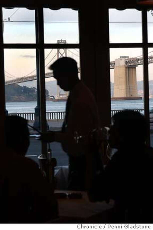 a waiter walks past the wiindow where guests sit, eat and enjoy the view of the Bay Bridge.  what used to be the Red Herring restaurnat is now Tonno Rosso. photo taken on 5/6/04 in San Francisco, CA.  must credit photo by Penni Gladstone/ Photo: Penni Gladstone