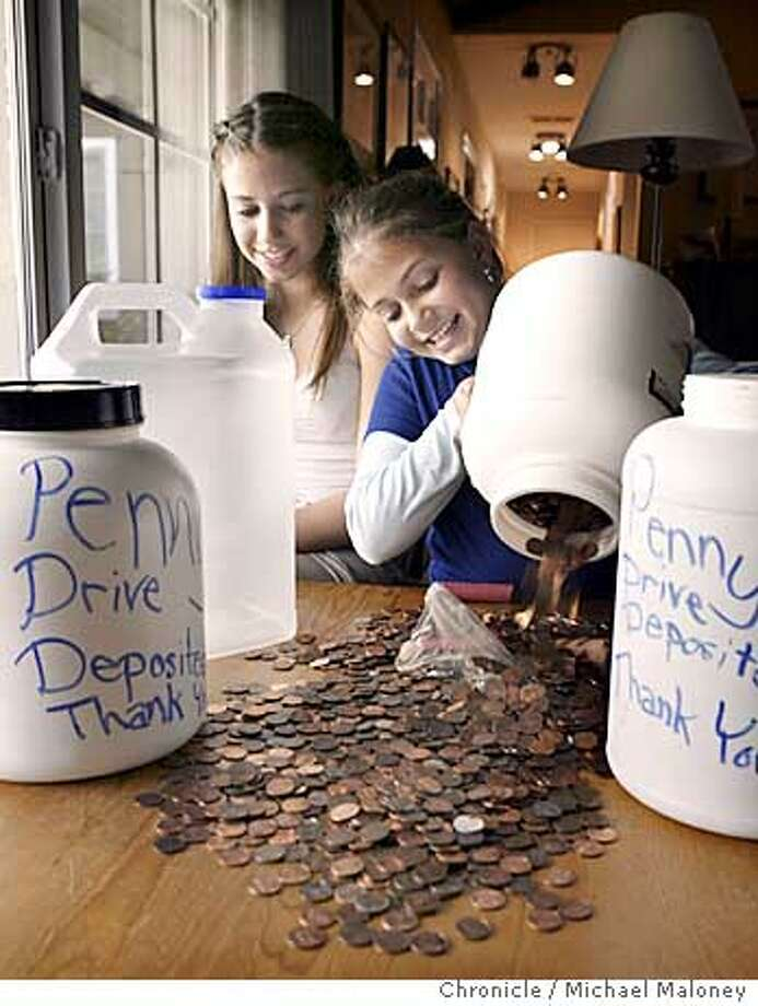 PENNIES_023_MJM.jpg  Zoe Oppenheim (right) pours some pennies out of a jar as her sister Emily looks on.  10-year-old Lafayette girl Zoe Oppenheim and her 15 year old sister Emily started a penny drive to raise money to save threatened programs in west Contra Costa schools. They and their dad distributed 500 flyers all over town and neighbors have been dropping by with sacks, jars, bags and pocketsful of pennies.Photo by Michael Maloney / The Chronicle Zo� Oppenheim (right) pours pennies out of a container, while her sister Emily watches. Zo� is leading a fund-raising drive for schools that are facing severe budget cuts. Photo: Michael Maloney