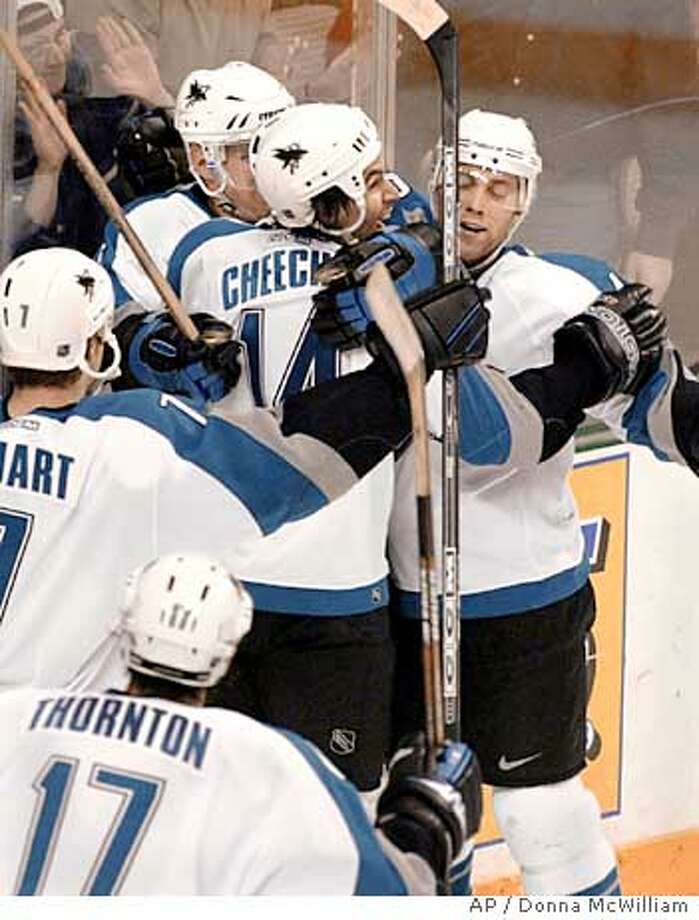 San Jose Sharks right wing Jonathan Cheechoo (14) celebrates with teammates Scott Thornton (17), Brad Stuart, left, Vincent Damphousse, back left, and Tom Preissing, right, after scoring the tying goal in the third period againg the Dallas Stars, Tuesday, March 16, 2004. The game ended in a 3-3 tie.(AP Photo/Donna McWilliam) Photo: DONNA MCWILLIAM