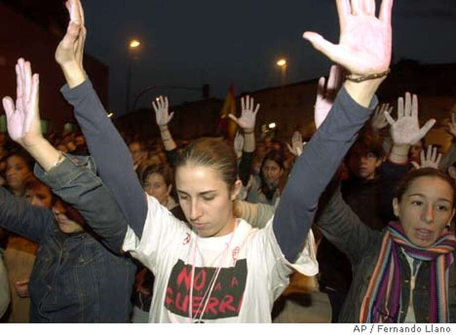 Protesters raise their arms during a silent march in Alcala de Henares, outside Madrid, Tuesday, March 16, 2004, to protest the bomb attacks on trains in the Spanish capital March 11, 2004, that killed 201 people and injured at least another 1,500. (AP Photo/Fernando Llano) Photo: FERNANDO LLANO