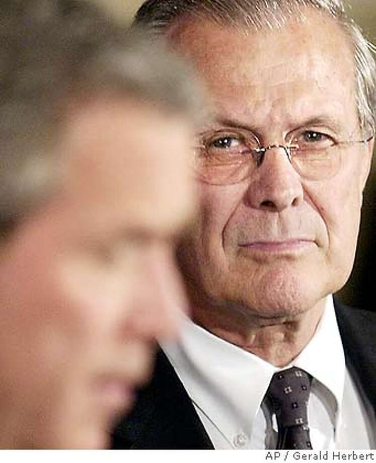 Defense Secretary Donald Rumsfeld listens as President Bush speaks at the Pentagon after a military briefing Monday, May 10, 2004. (AP Photo/Gerald Herbert) Photo: GERALD HERBERT