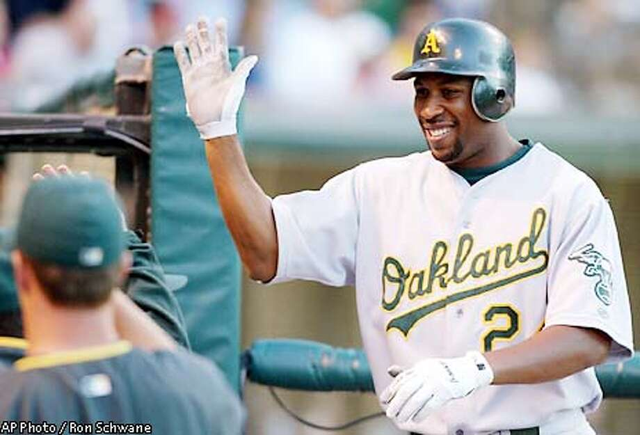 Oakland Athletics' Jermaine Dye celebrates his three-run home run off Cleveland Indians pitcher Jake Westbrook as he enters the dugout in the third inning at Jacobs Field, Tuesday, Aug. 20, 2002, in Cleveland. (AP Photo/Ron Schwane) Photo: RON SCHWANE