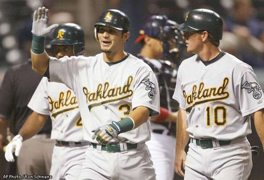 Oakland Athletics' Eric Chavez, center, celebrates his three run home run off Cleveland Indians pitcher Mark Wohlers with Miguel Tejada, left, and Scott Hatteberg, right, in the ninth inning at Jacobs Field Monday, Aug. 19, 2002, in Cleveland. Chavez hit two home runs on the night and helped the A's to a 8-1 victory. (AP Photo / Ron Schwane) Photo: RON SCHWANE
