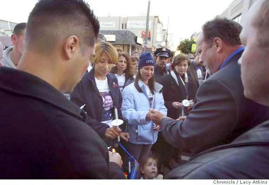 Isaac Espinoza's widow Renata, left in white t-shirt, attends a candlelight vigil Monday night to support SF police officers. Marchers gathered in front of Hall of Justice in San Francisco, Ca., at 7:30 p.m. and then start walking to SF City Hall at 8 p.m. Photo taken on 5/10/04 in San Francisco, CA. Photo by Lacy Atkins / The San Francisco Chronicle Photo: LACY ATKINS