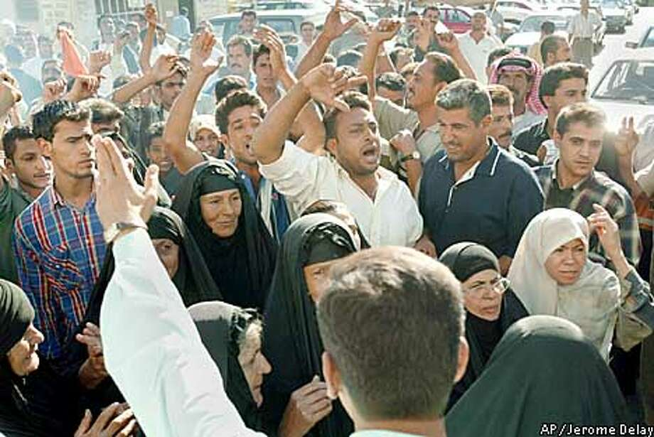A ministry of information official, foreground, asks demonstrators to clear the area, as relatives of Iraqi prisoners, unaccounted for after Saddam Hussein's amnesty decree , demonstrate in front of the information ministry building in Baghdad on Tuesday, Oct. 22, 2002. On Sunday, the government invited foreign reporters to witness hundreds or thousands of prisoners being released _ most apparently common criminals _ but it remained unclear Tuesday how many were freed. (AP Photo/Jerome Delay) Photo: JEROME DELAY