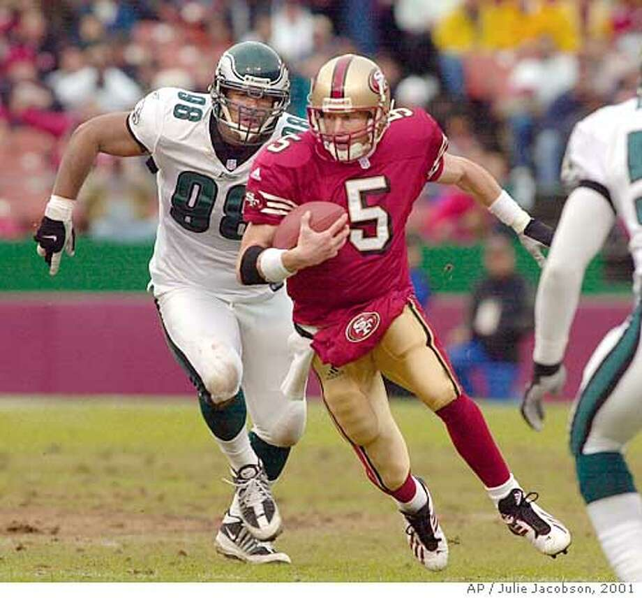 San Francisco 49ers quarterback Jeff Garcia avoids Philadelphia Eagles defensive end Brandon Whiting on his way to a first down during the first quarter Saturday, Dec. 22, 2001 in San Francisco. (AP Photo/Julie Jacobson) Photo: JULIE JACOBSON