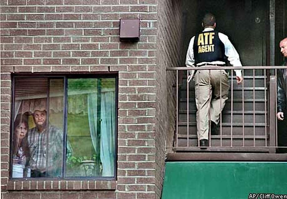 Residents of an apartment complex near the bus stop where a Montgomery County RideOn bus driver was shot early Tuesday, Oct. 22, 2002, in the Aspen Hill section of Silver Spring, Md. gaze out their window towards the crime scene as ATF agents go door-to-door seeking information about the crime. (AP Photo/The Washington Times, Cliff Owen ) ** MAGS OUT WASHINGTON POST OUT NEW YORK TIMES OUT ** Photo: CLIFF OWEN