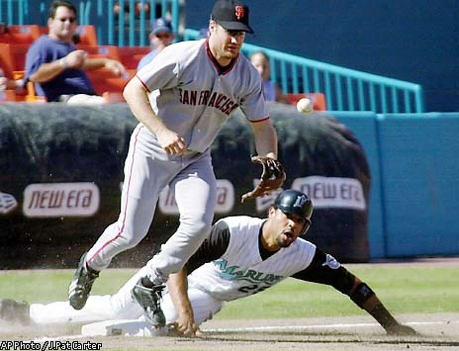 Florida Marlins' Derrek Lee (25) slides safely into third base as San Franscisco Giants third baseman David Bell chases the ball on a bad throw from the pitcher during the second inning in the Sunday, Aug. 18, 2002 game in Miami. (AP Photo/J.Pat Carter) Photo: J. PAT CARTER
