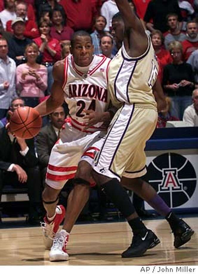 Arizona's Andre Iguodala (24) drives around the attempted defense of Washington's Bobby Jones (15) for a shot during the first half at McKale Center in Tucson, Ariz. on Thursday, Feb. 26, 2004. (AP Photo/John Miller). Washington beat Arizona three times this season, and the eighth-seeded Huskies' athleticism makes them dangerous. Photo: JOHN MILLER