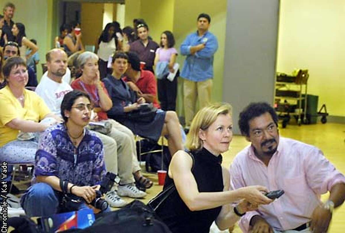 Carlos Mauricio (right) and his wife, Ruth Goode, play the news clips of the trial during a party at the Women's Building in San Francisco to celebrate the case where Mauricio, a science teacher at SF's Balboa High School, and two other Salvadoran torture victims were just awarded $54.6 million dollars. SAN FRANCISCO CHRONICLE PHOTO BY KAT WADE