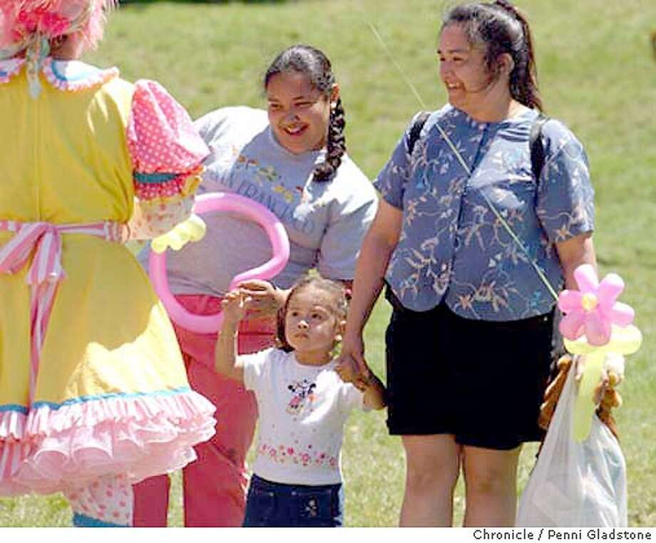 at left is Pinkie the clown, who is making baloon flowers, animals etc. for the kids. at left is 11 yr old Yara Lopez (at rt is her aunt Micaela), 2 yr old Gloria Perez and her mom Micaela Andrade. They are going to have a BBQ for mother's day with other family members.  Mother's Day at Doloras Park  photo taken on 5/9/04 in San Francisco, CA.  must credit photo by Penni Gladstone/ Photo: Penni Gladstone