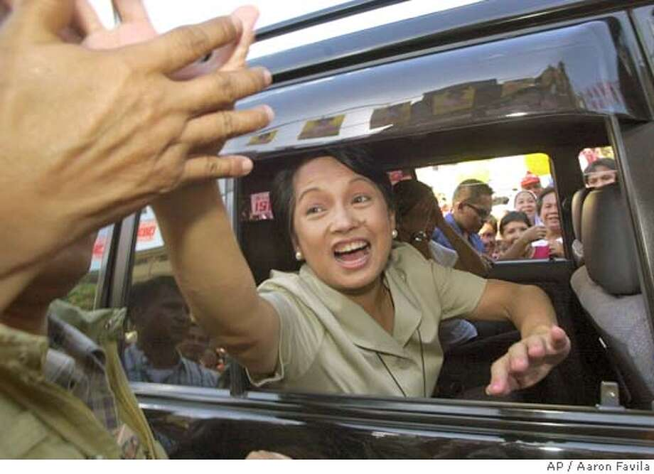 Philippines President Gloria Macapagal Arroyo reaches out from a car window to supporters as she campaigns in the Tondo slum area in Manila Thursday, May 6, 2004. Arroyo is running a dead heat battle with a popular actor candidate Fernando Poe, Jr. to get the mandate in the May 10 presidential polls. (AP Photo/Aaron Favila) Photo: AARON FAVILA