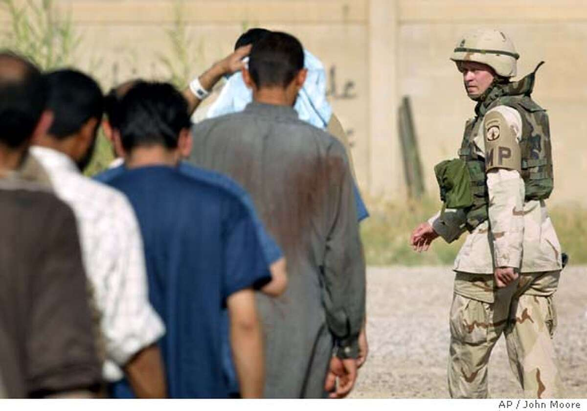 A U.S. Army military policeman leads a group of fresh detainees for interrogation inside the Abu Ghraib Prison on the outskirts of Baghdad, Iraq Saturday, May 8, 2004. American soldiers now at the prison arrived months after photos were taken showing prisoner abuse in late 2003.(AP Photo/John Moore)