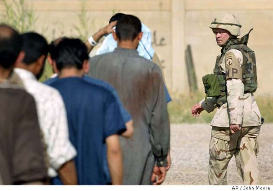 A U.S. Army military policeman leads a group of fresh detainees for interrogation inside the Abu Ghraib Prison on the outskirts of Baghdad, Iraq Saturday, May 8, 2004. American soldiers now at the prison arrived months after photos were taken showing prisoner abuse in late 2003.(AP Photo/John Moore) Photo: JOHN MOORE