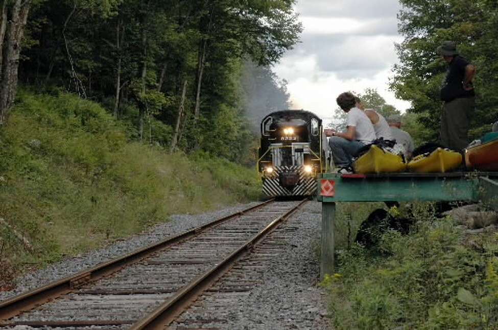 The Adirondack Scenic Railroad approaches a platform near the Moose River near Old Forge, where kayaker and canoeists wait to board. The railroad wants one day to operate all the tracks it leases from the state between Utica and Lake Placid, but hikers and snowmobilers want to turn unused parts fo the line into a recreational trail in the heart of the Adirondacks.