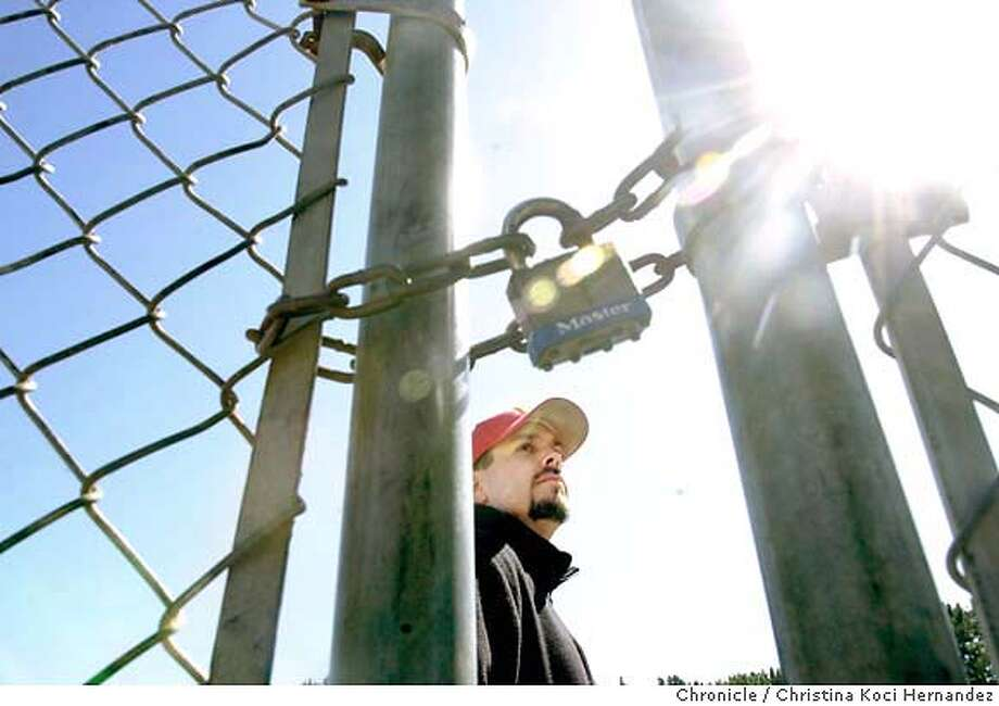 westcoco14a_031204_kocihernandez  CHRISTINA KOCI HERNANDEZ/CHRONICLE Perelli stands on baseball field, behind locked gate.At De Anza High, in El Sobrante, P.E. teacher, Joe Perelli, faces being laid off, with the current threats of cutting all sports programs. We are working a series of profiles of teachers in the West Contra Costa School District and need portraits of the people we're profiling. Joe Perelli, athletic director at De Anza High School in El Sobrante, got a layoff notice after the school district cut all sports. Photo: CHRISTINA KOCI HERNANDEZ