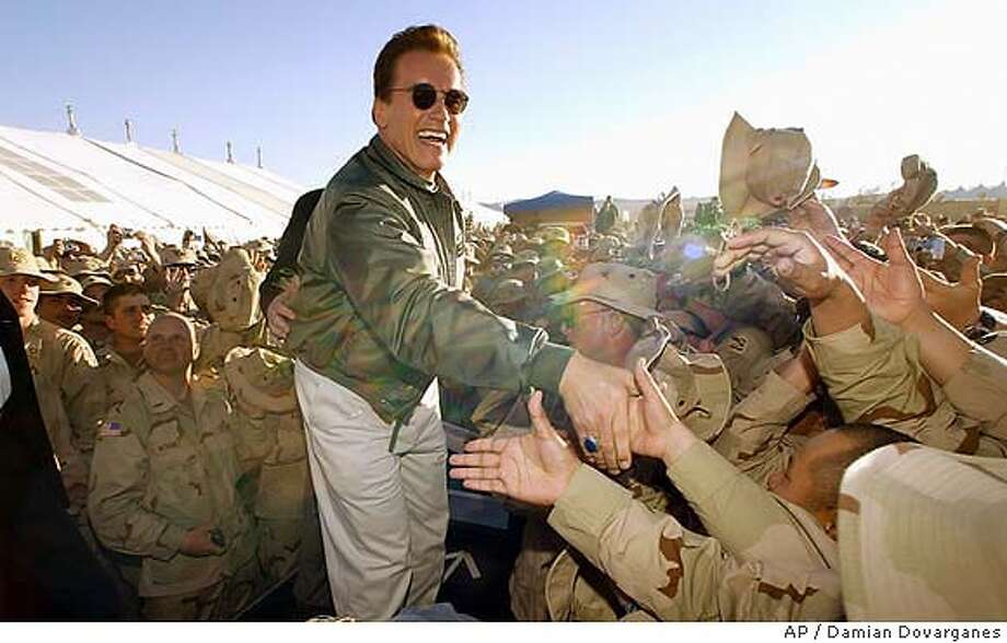 "Gov. Arnold Schwarzenegger shakes hands Friday, March 12, 2004, with about 700 Army National Guard troops preparing to deploy to Iraq, during a visit to the army's National Training Center in Fort Irwin, Calif. Schwarzenegger's appearance came as members of the National Guard's 81st Separate Armor Brigade was gearing up to head to Iraq, where they will conduct security operations, serve as military police and provide humanitarian assistance.""I play a machine, but you guys are the true machines. You're the true terminators,"" Schwarzenegger said, standing before a backdrop of Army tanks and soldiers. (AP Photo/Damian Dovarganes) Gov. Arnold Schwarzenegger greets members of the National Guard at Fort Irwin. He spoke of his time in the Austrian military. Photo: DAMIAN DOVARGANES"