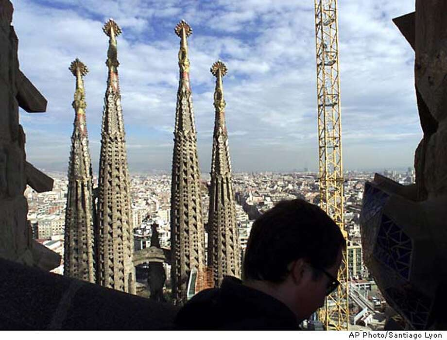 TRAVEL BARCELONA, Spain -- A tourist walks on a new tower of the Holy Family temple (La Sagrada Familia) designed by Catalan architect Antonio Gaudi, Jan. 23, 2002. Work continues on the church which was started in 1883. This year marks the 150th anniversary of Gaudi's birth. (AP Photo/Santiago Lyon) Photo: SANTIAGO LYON