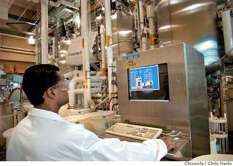 genentech30040_CH.jpg  Story on Genentech, this is the Pilot Plant with plant supervisor Bijee George checking the progress of the fermentation.  11/25/03 in South San Francisco. CHRIS HARDY / The Chronicle Supervisor Bijee George checks the progress of fermentation inside vats at Genentech's plant in South San Francisco. Photo: CHRIS HARDY