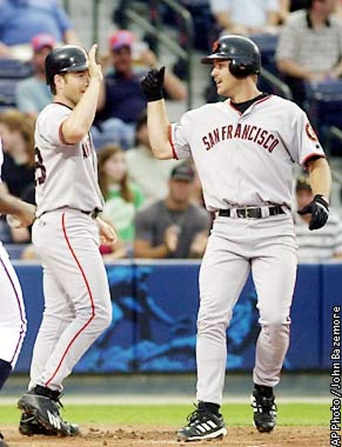 San Francisco Giants' Jeff Kent, right, is congratulated by teammate David Bell after hitting a two-run home run off Atlanta Braves starter Damian Moss in the first inning in Atlanta Thursday, Aug. 15, 2002. (AP Photo/John Bazemore)