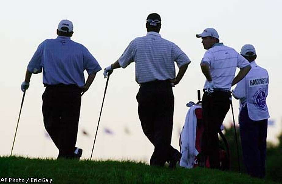 Mark Calcavecchia, Chris DiMarco, Padraig Harrington, and Harrington's caddie, David McNeilly, left to right, wait on the 18th tee late during the first round of the at Hazeltine National Golf Club in Chaska Minn., on Thursday, Aug. 15, 2002. A suspension of play earlier in the day because of thunderstorms prevented 39 players from completing their first round. (AP Photo/Eric Gay) Photo: ERIC GAY