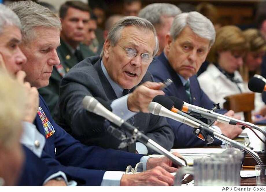 Defense Secretary Donald Rumsfeld gestures as he answers a question asked by a House Armed Services Committee member during the committee hearing on Capitol Hill Friday, May 7, 2004, on prisoner abuse in Iraq. At left, Gen. Richard Myers, Chairman of the Joint Chiefs of Staff, and right, Les Brownlee, acting Secretary of the Army. (AP Photo/Dennis Cook) Photo: DENNIS COOK