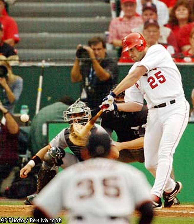Anaheim Angels' Troy Glaus hits a home run as San Francisco Giants shortstop Rich Aurilia (35) and catcher Benito Santiago watch in the second inning of Game 1 of the in Anaheim, Calif., Saturday, Oct. 19, 2002. (AP Photo/Ben Margot) Photo: BEN MARGOT