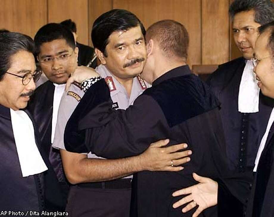 Former East Timor police chief Brig. Gen. Timbul Silaen, center, is congratulated by his lawyers after his trial at a court in Jakarta Thursday, Aug. 15, 2002. A Jakarta court Thursday acquitted the Indonesia's last police chief in East Timor on charges of allowing five massacres of civilians in the province during its tumultuous break with Indonesia in 1999. (AP Photo/Dita Alangkara) Photo: DITA ALANGKARA
