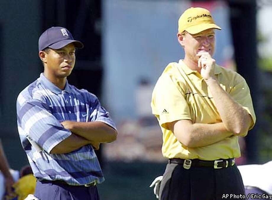Tiger Woods and Ernie Els wait on playing partner David Toms after finishing the first round of the PGA Championship Thursday, Aug. 15, 2002 at Hazeltine National Golf Club in Chaska, Minn. Woods finished at one-under and Els finished even. (AP Photo/Eric Gay) Photo: ERIC GAY