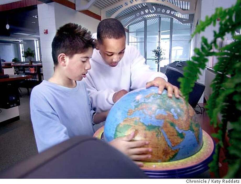 SHOWN: L to R: Edgardo Cervantes, age 11, and Amir Woodword, 12, take a look at the globe during their 6th grade class's visit to the library. We visit the brand new library at Richmond's (CA) brand new Lavonya DeJean Middle School, which stands to be closed due to $16.5 in cuts approved by the West County School Board this week. Writer is Simone Sebastian. Katy Raddatz / The Chronicle Photo: Katy Raddatz