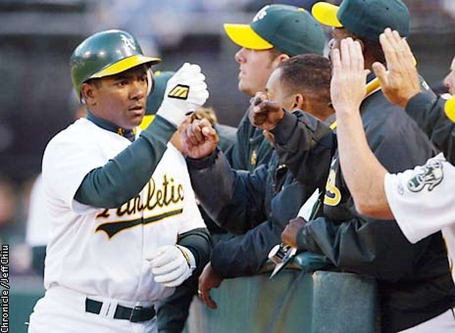 ATHLETICS24M-C-23APR02-SP-JC-- Miguel Tejada is greeted by teammates after his solo homerun in the second inning as the New York Yankees play the A's on Tuesday night. Photo by Jeff Chiu / The Chronicle.