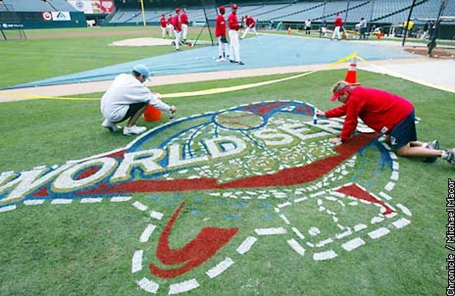 Sean McMenamin and Mike Clark, right, put the finishing touches on the 2002 World Series logo between home and third base at Edison Field October 18, 2002. The San Francisco Giants vs. the Anaheim Angels in the World Series with games one and two being played in Anaheim. Michael Macor/San Francisco Chronicle Photo: Michael Macor
