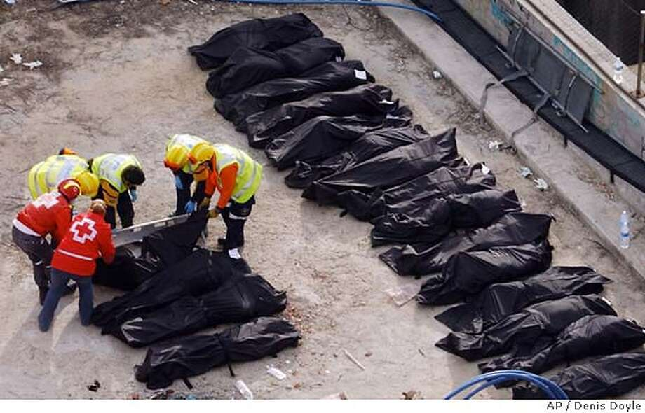 Rescue workers line up bodies beside a bomb damaged passenger train at Atocha station following a number of explosions on trains in Madrid Thursday March 11, 2004, just three days before Spain's general elections, killing more than 170 rush-hour commuters and wounding more than 500 in Spain's worst terrorist attack ever. (AP Photo/Denis Doyle) Rescue workers line up bodies of victims outside a bombed passenger train at the Atocha station in Madrid. Photo: DENIS DOYLE