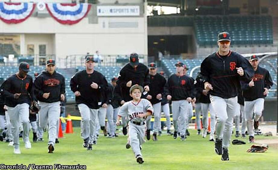 GIANTS13-C-18OCT02-MT-DF.jpg---Giants Jeff Kent and his son Hunter lead the Giants in there warm-ups during the start of team practice at Edison Field. The San Francisco Giants vs. the Anaheim Angels in the World Series with games one and two being played in Anaheim. Deanne Fitzmaurice/San Francisco Chronicle