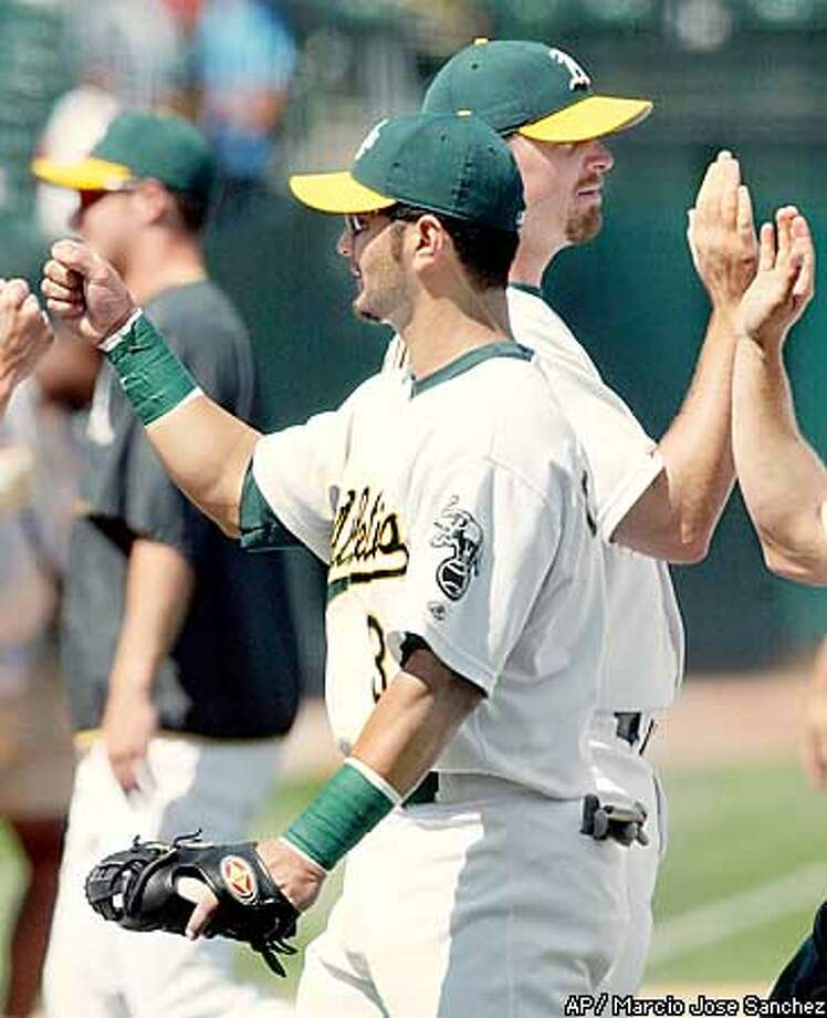 Oakland Athletics third baseman Eric Chavez, center, high fives teammates at the end of their 4-2 win over the Toronto Blue Jays at Network Associates Coliseum in Oakland, Calif., Wednesday Aug., 14, 2002. Chavez drove in three of the A's four runs in the game with a three-run home run in the first inning. (AP Photo/Marcio Jose Sanchez) Photo: MARCIO JOSE SANCHEZ