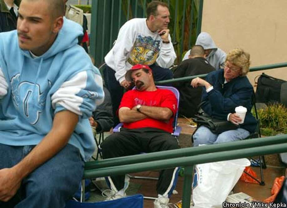 "Angels fans, including Bob ""Angel Bob"" Sheinblum, resting in his seat, wait at Edison Field in Anaheim for World Series tickets. Chronicle photo by Mike Kepka"